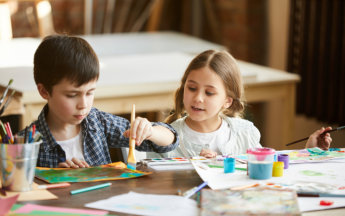Portrait of two children boy and girl painting together sitting at table at home