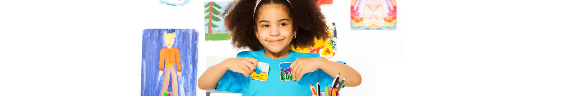 Cute African girl playing developmental game holding cards matching relation by table sitting in playroom